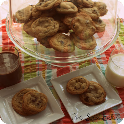 Chocolate chip cookies piled high on a serving tray with two plates put out with cookies on them.