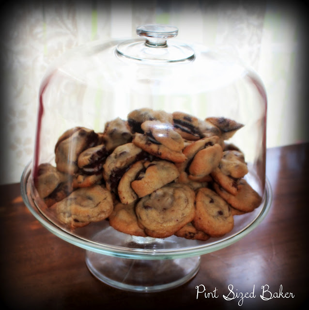 A photo of the cookies on a cake platter with a glass dome.