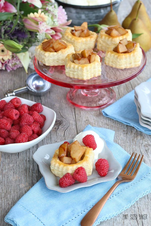 A serving of Pear Puff Pastry Tart on a dish with fresh red raspberries, setting in front of a cake stand full of puff pastry desserts.