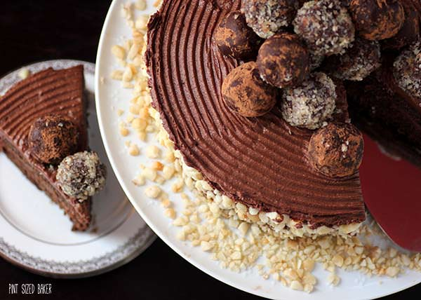 A perfect cake -Combed chocolate frosting with macadamia nuts around the perimeter and topped with truffles.