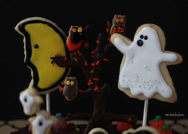 "Cookie Ghosts and a chocolate ""tree"" with spooky owls decorate a Halloween Graveyard Cake."