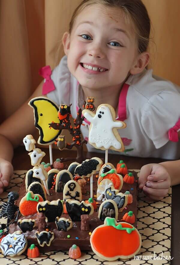 Grab your little ghouls and witches to make this fun Halloween Graveyard Cake with cookie decorations.