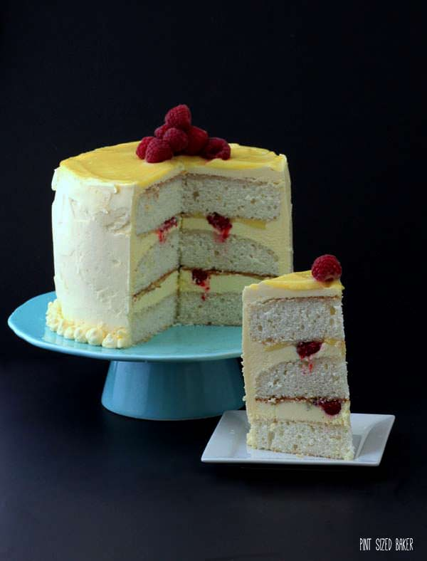 Lemon sponge cake with homemade layer curd and pops of fresh raspberries. This Raspberry and Lemon Layer Cake is simply stunning!