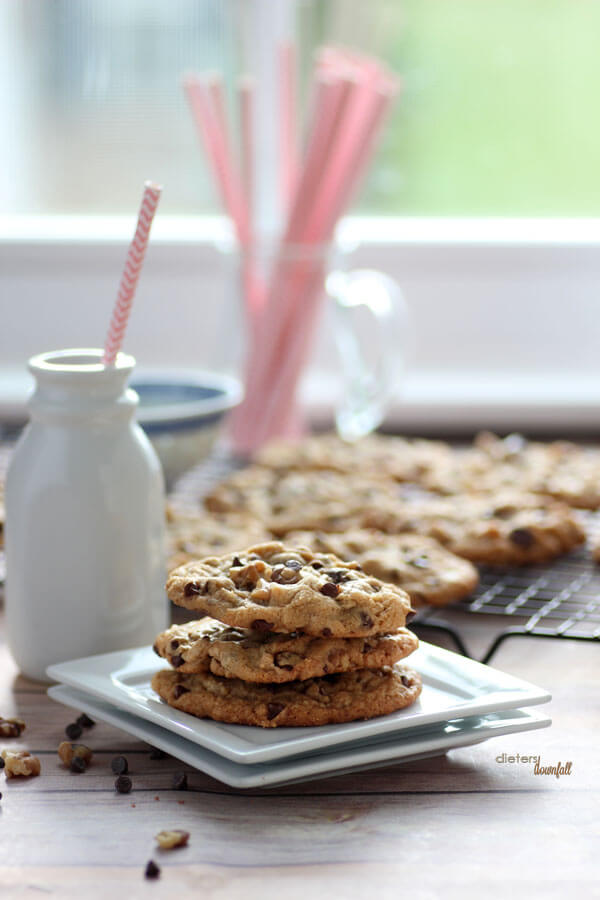 A plate of three Chocolate Chip and Walnut stuffed Cookies stacked up with a bottle of milk.