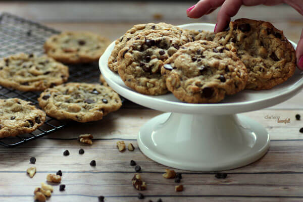 A photo of a hand picking up a classic Chocolate Chip Cookie from a platter.