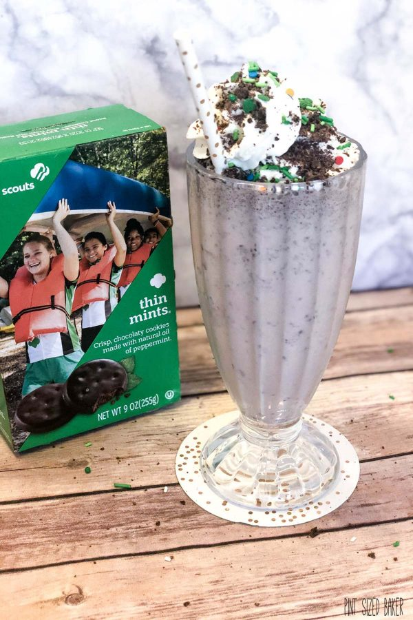 A box of Girl Scout Thin Mints sit behind the milkshake made with the cookies.