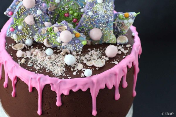 details of the top of the cake showing the pink drip, unicorn candy bark, and crushed candies.