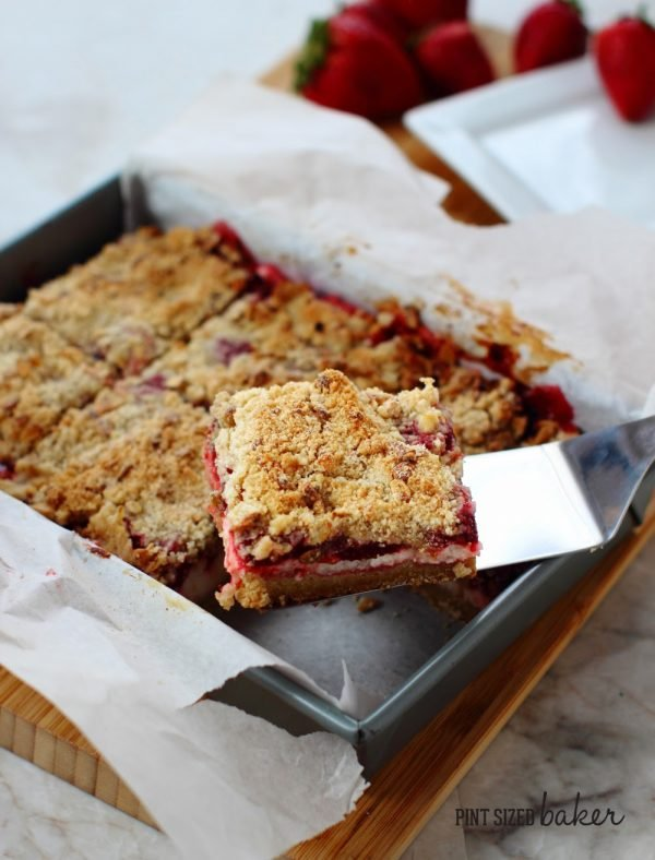 Removing the strawberry bars from the baking pan.