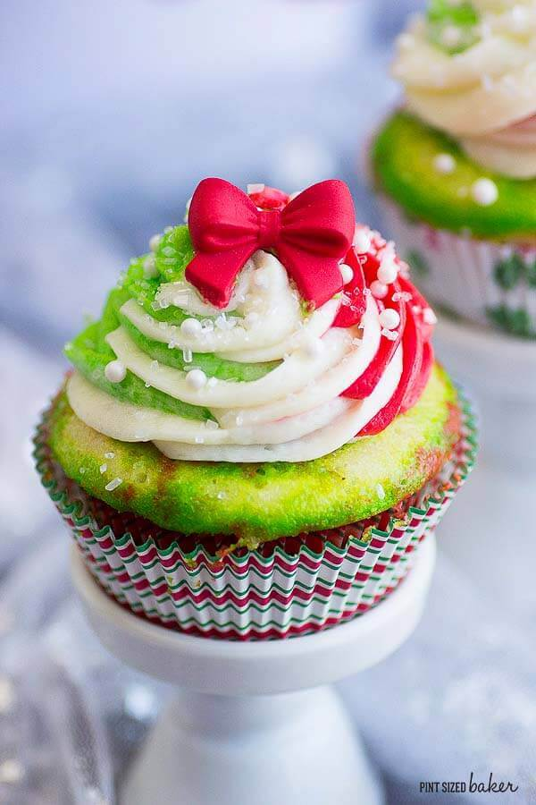Perfect Christmas Cupcakes with easy red, green, and white frosting. Topped with a pretty bow and sprinkles.