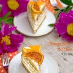 Light and fluffy layers of Orange Olive Oil Cake with whipped cream frosting and a candied orange slice on top.