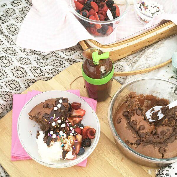 Picnic Chocolate Cake with fresh fruit, whipped cream and chocolate sauce all served at the park.