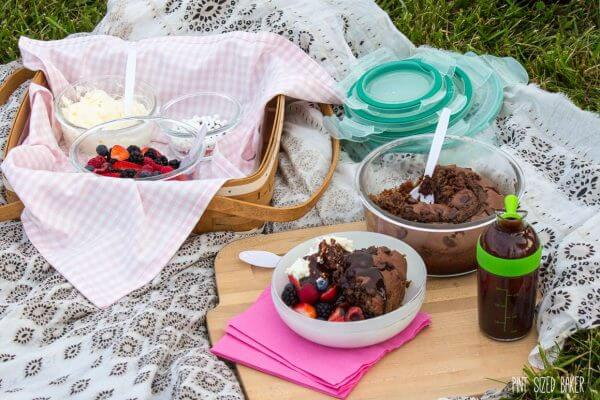 Chocolate cake, fresh fruit, whipped cream and chocolate sauce all packed up and brought on a picnic outing.