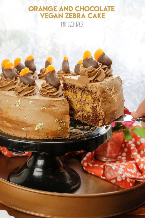 """Lead in image with the text """"Orange and Chocolate Zebra Vegan Cake"""" and a slice of the cake being removed to show off the zebra design inside."""