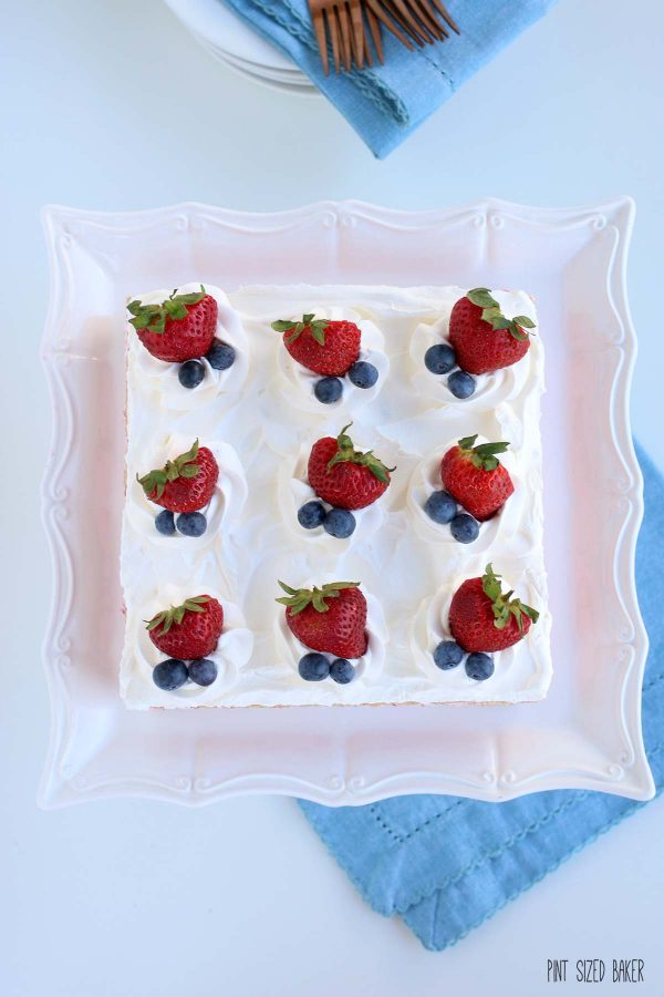 Overhead view of an Icebox Cake Recipe with fresh strawberries and blueberries on a pedestal stand.