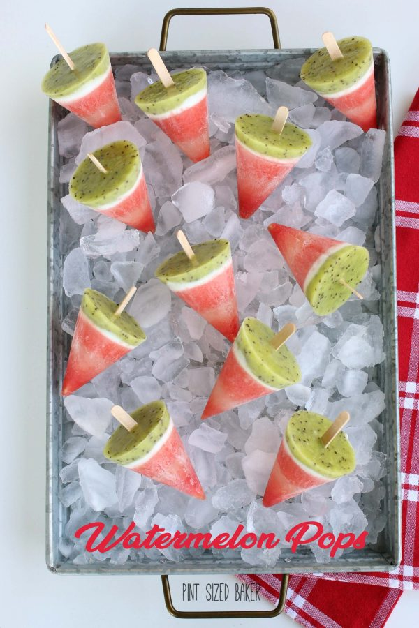 Overhead view of frozen watermelon pops shown on a tray of ice.