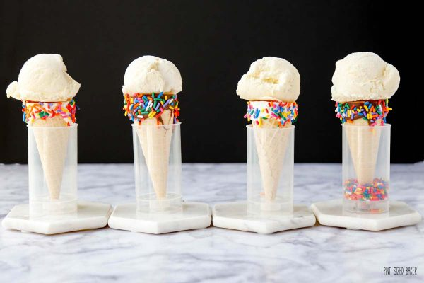 four vanilla ice cream cones lined up in a row