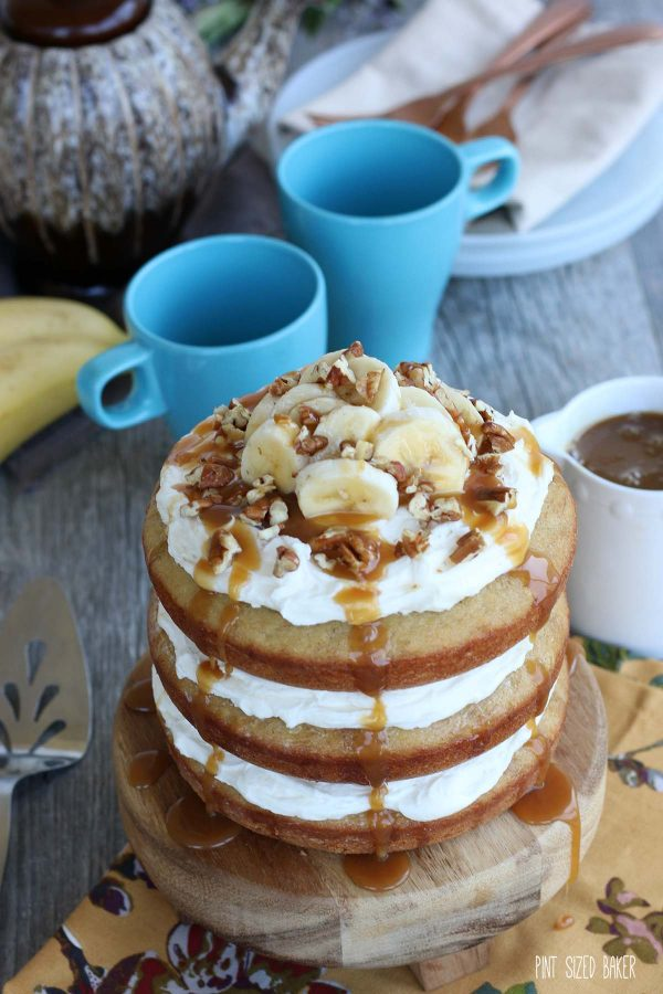 Banana naked cake recipe is finished and presented on a cake stand with coffee cups in the background.