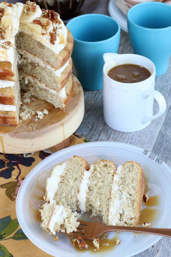 Slice of banana naked cake on a plate with a bite out of it and a jar of caramel sauce in the background.