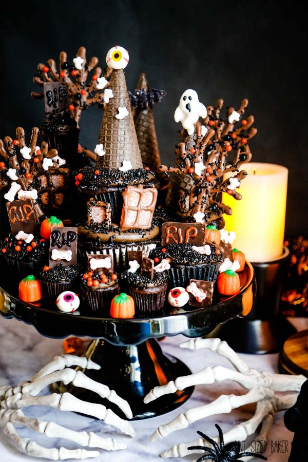 Chocolate cupcakes decorated like a haunted house on a black cake platter with skeleton hands at the bottom.