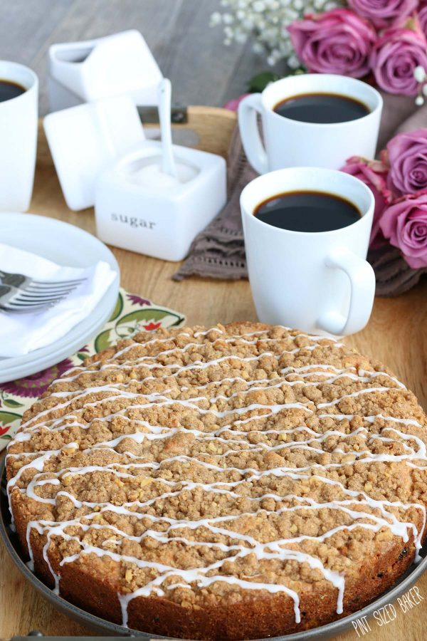 A rum raisin coffee cake with white icing drizzled on top sitting on a wooden cutting board in front of three cups of coffee.