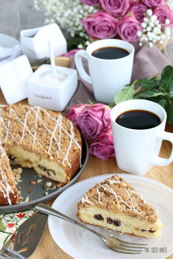 Photo of a table with two coffee cups and a coffe cake with a slice removed and served on a plate. Mauve roses and baby's breath in the background.