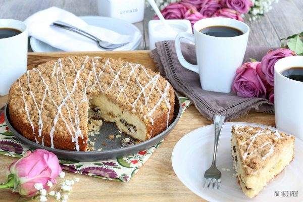 A place setting photo with cups of coffee and a slice of coffee cake.