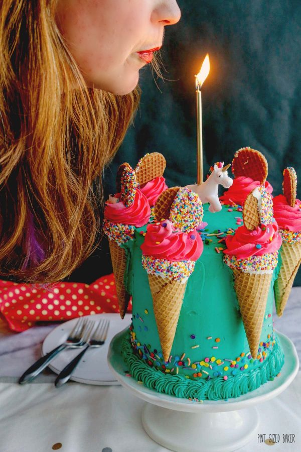 A photo of Pint Sized Baker blowing out the candle on a teal and pink birthday cake.