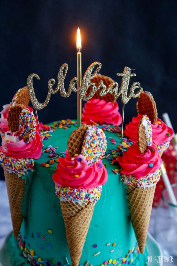 An image of the teal birthday cake with ice cream cones filled with pink buttercream and a lit candle on top.