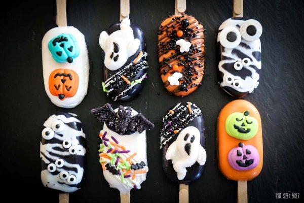8 Halloween Cakesickles on a black platter.