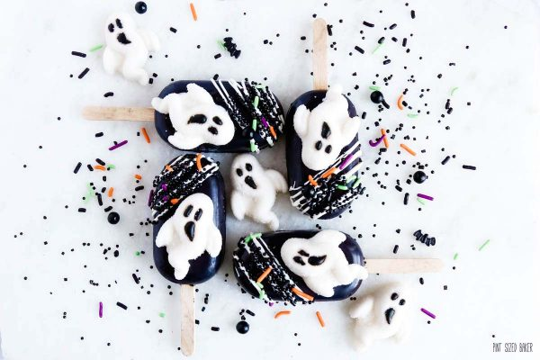 White ghost candies on black cakesickles with black sprinkles.