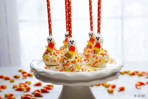 a photo Halloween cake pops on a platter with candy corns on the table.