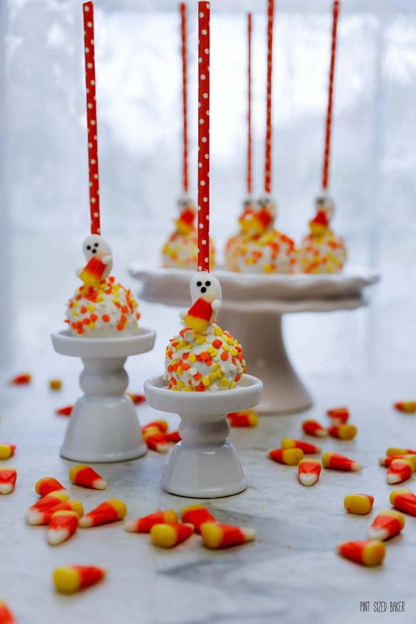 An image of Halloween cake pops with orange straws on a serving platter.