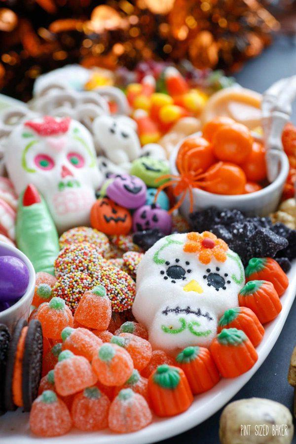 Sugar skull marshmallow and candy pumpkins on a Halloween platter.