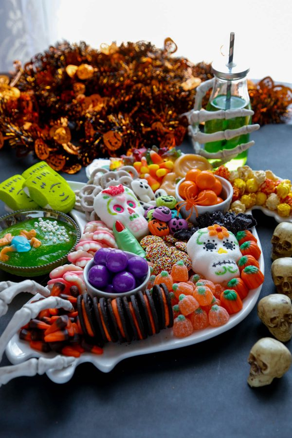 Halloween Candy covering a ghost platter with skeleton hands holding a green drink.