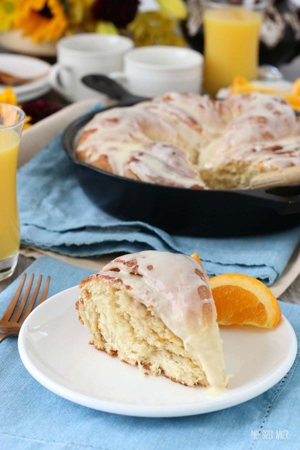 A slice of breakfast bread on a plate with an orange slice. Orange bread twist goes great with other breakfast favorites.