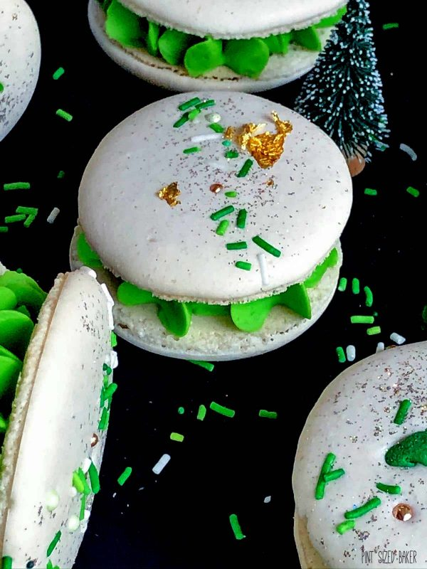 "A close up image of the Macarons to show off the ""feet"", buttercream ruffle, and green Christmas sprinkles."