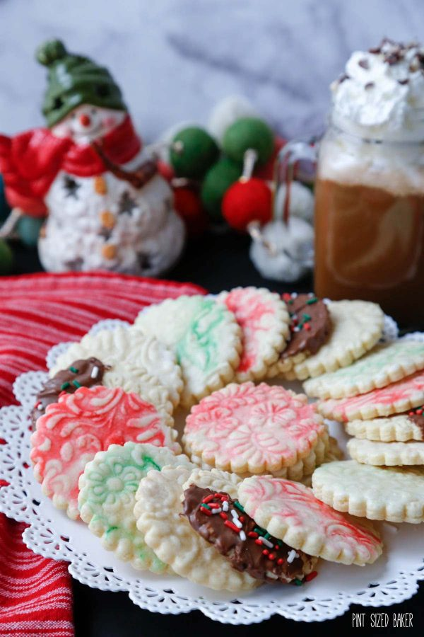 Image of the Embossed Shortbread Cookies on a cookie platter with hot chocolate and Christmas ornaments in the background.