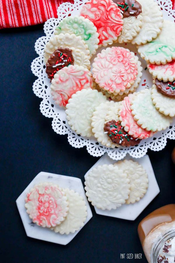 An overhead image of the embossed cookies on a cookie plater with a few on marble plates.