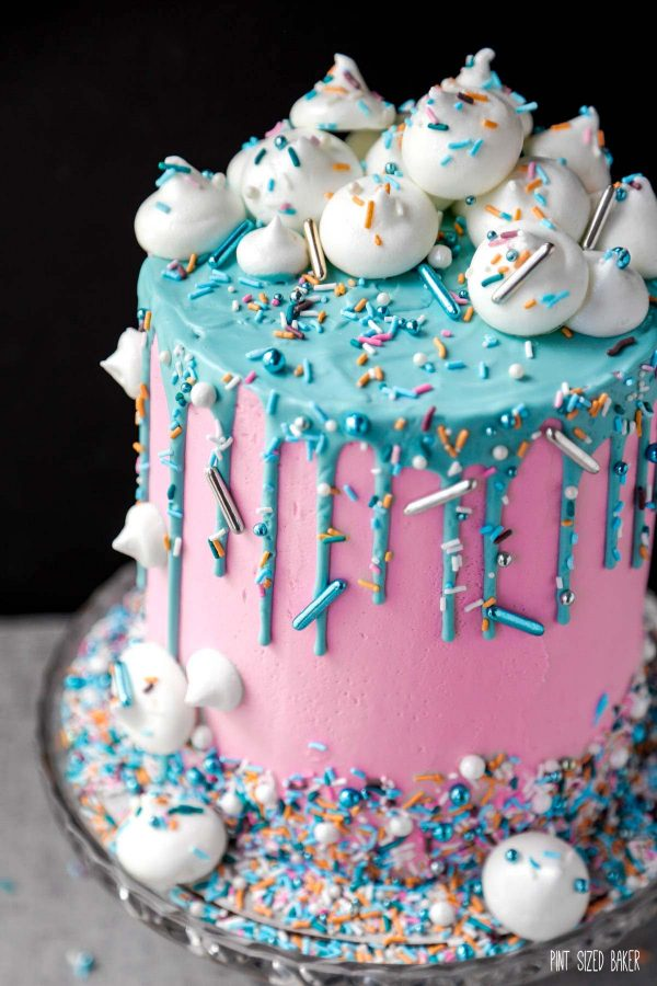 A cake covered in pink buttercream with teal ganache drip covered in fun Maui Christmas sprinkle medley.