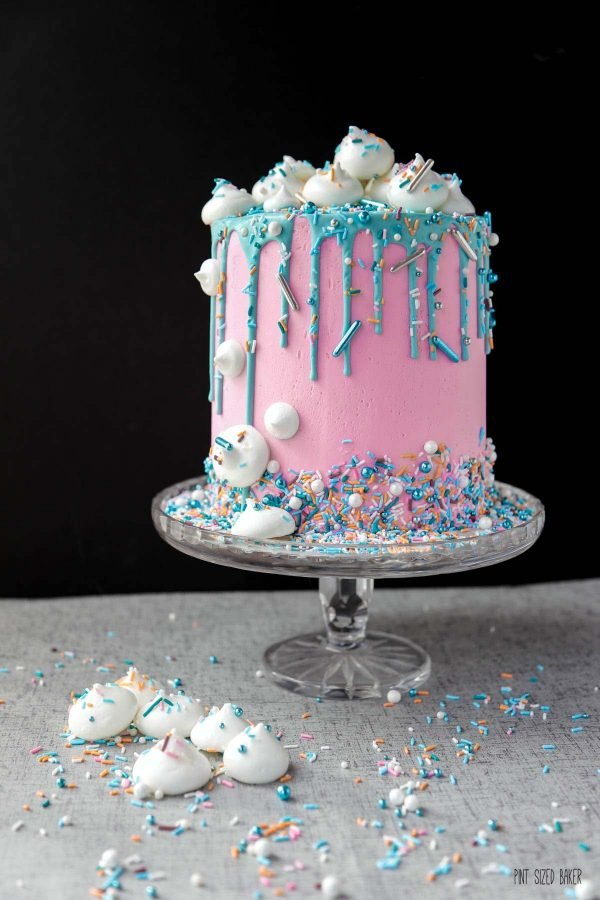 This 6-inch diameter cake is 6 cake layers tall, covered in pink buttercream and decorated with a teal drip and meringue treats.