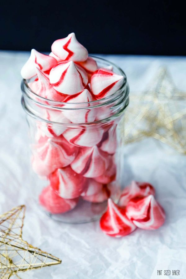 A photo of the red and white meringue cookies in a glass mason jar.
