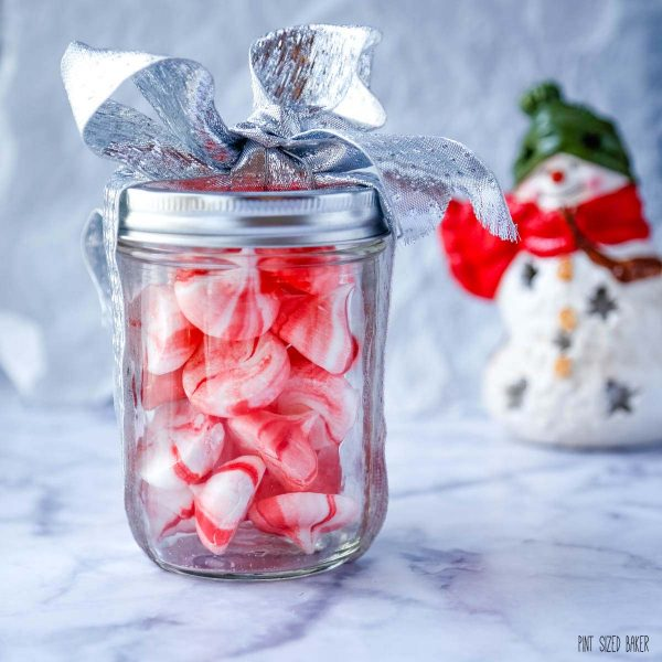 An image of the candy peppermint meringues all packaged up in a glass jar with a silver ribbon.