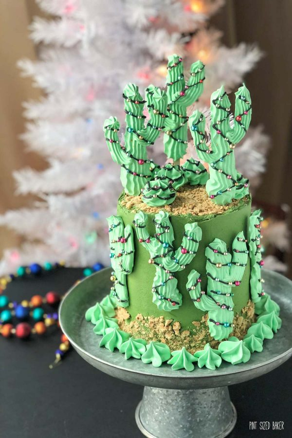 Decorated for the holidays, Saguaro Cacti decorate a moss green cake with a Christmas tree in the background.
