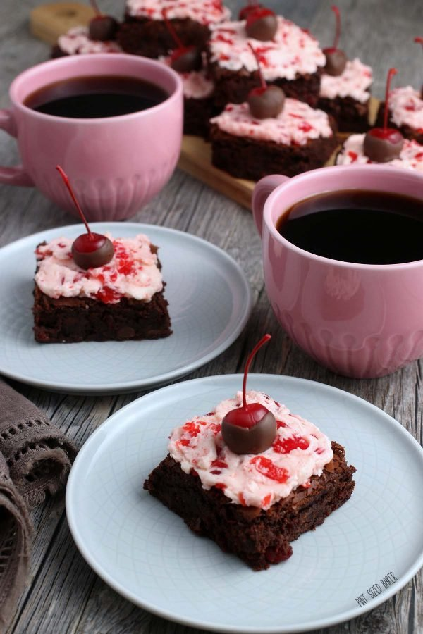 Two plates of chocolate cherry brownies with two pink mugs of coffee with a tray of brownies in the background.
