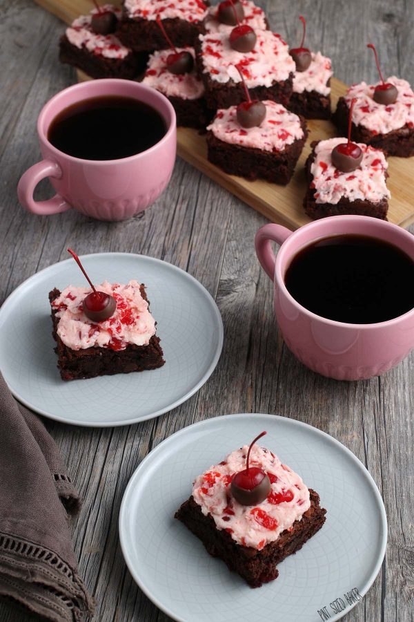 Two plates of chocolate cherry brownies with two pink mugs of coffee.