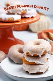 A plate piled high with three Baked Pumpkin Donuts with cinnamon sugar glaze.