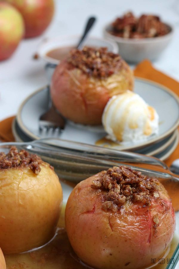 A close up image of the baked apples in the baking dish with a plate in the background ready to serve.