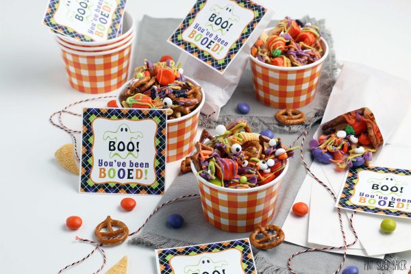 A horizontal image of the Halloween snack mix in orange and white gingham paper bowls.