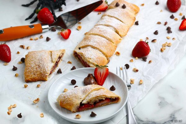 A horizontal image of the pastry wrap with sliced strawberries, chocolate chips, and hazelnut pieces.