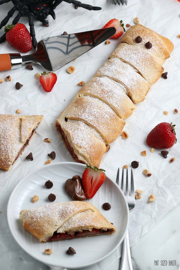 A photo of the sliced Halloween Calzone with sliced strawberries and a fake spider.